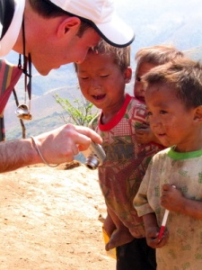 An American tourist shows photos to local hilltribe boys